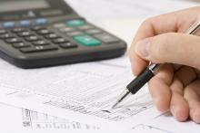 A hand with a pen filling out tax forms with a calculator in the back